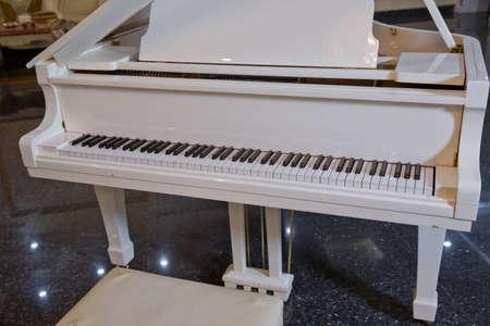 Frühlingsklavierdekor. Weißes Klavier und Stuhl. weißes Klavier in der Halle .Piano conner zum Entspannen und Musizieren.