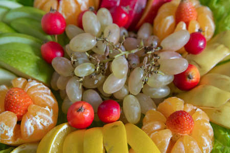 Fruit background .White grapes, red apples, tangerines, strawberries, lemons. Fresh fruits.Assorted fruits colorful background.slices of colourfull fruits Foto de archivo - 129927893