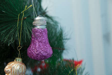 Violet brilliant sphere hangs on a branch of a New Years fir-tree . Branches Christmas lamp ball . New year background decorations Christmas tree green nature Christmas ball . Christmas ball hanging