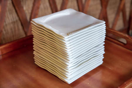 Contemporary square white plates stacked . White square porcelain plates in large quantities on the counter of a store in artificial light. Reklamní fotografie