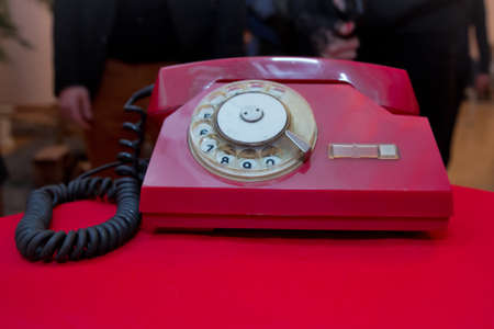 Red antique vintage analog telephone dialing or scrolling phone on red table. Contact us concept .Still life with retro red phone on wooden red table over grunge background