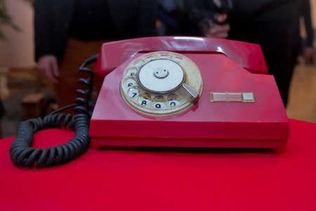 Rotes antikes analoges Telefon der Weinlese, das Telefon auf rotem Tisch wählt oder scrollt. Kontaktieren Sie uns Konzept. Stillleben mit Retro-rotem Telefon auf rotem Holztisch über Grunge-Hintergrund