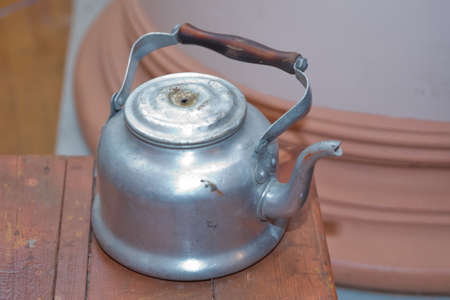 Old aluminum tea kettle with lid . An old slightly damaged aluminum kettle . old-fashioned aluminum kettle top . large tea pot kettle aluminum . Reklamní fotografie