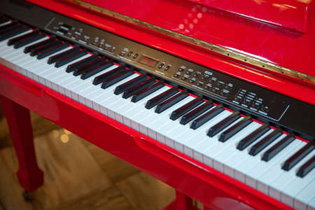 Red piano keyboard with glossy black and white keys as a music background in wide panoramic banner format, selected focus, narrow depth of field