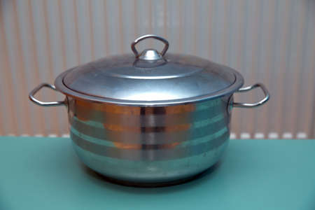 A stainless steel pot on a green background . Metal pan Stock fotó