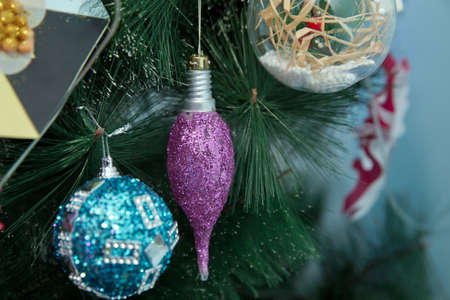 Violet brilliant sphere hangs on a branch of a New Years fir-tree . Branches Christmas lamp ball . New year background decorations Christmas tree green nature Christmas pink and blue ball .