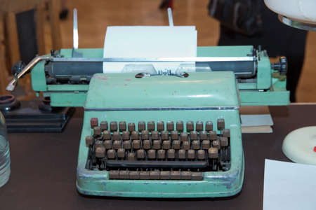 Retro typewriter . A printing press is a mechanical device for applying pressure to an inked surface . close up of typewriter vintage retro styled . Typewriter with sheet of paper