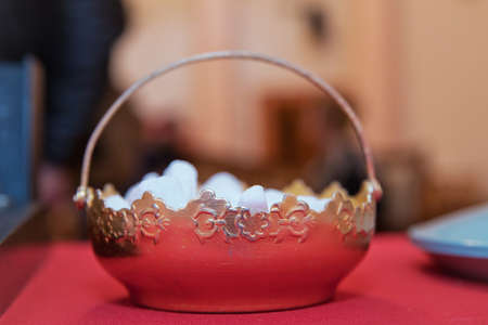 Ancient sugar bowl .sugar bowl with a lump sugar isolated on a red background . Silver sugar bowl 写真素材