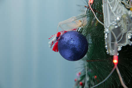 Christmas ball on the branches fir. Photo Christmas blue ball on a Christmas tree branch on a background of the night city lights 스톡 콘텐츠 - 129927948