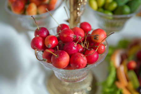 Hand dipped caramel crab apples . Red crab apple in a glass jar