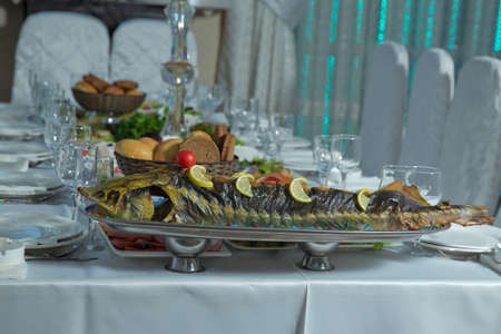grilled fish . Cooked fish is on the table .Grilled sturgeon fish. Grilled sturgeon fish. Healthy food.bread, sausage, salad. Sturgeon baked with vegetables. Healthy food.