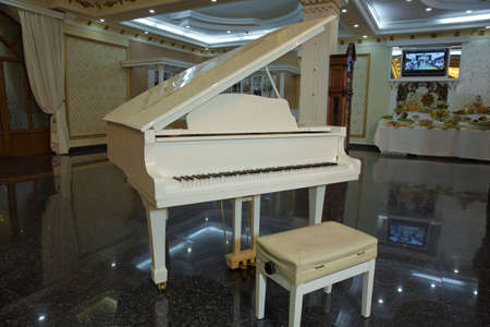 white piano in the hall .Piano conner for relax and playing music. spring piano decor . Stock fotó