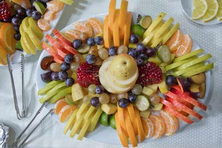 sliced fruits are inside the plate. Mandarin, grape, pomegranate, apple, orange Acca sellowiana