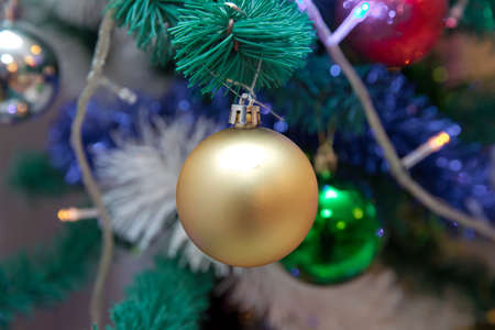 Photo Christmas gold ball on a Christmas tree branch on a background of the night city lights . Christmas ball on the branches fir.