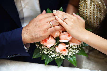 A bride and groom show off their wedding rings by placing their left hands on the brides bouquet . A newly engagement couple place their hands on a wedding bouquet showing off their wedding rings.