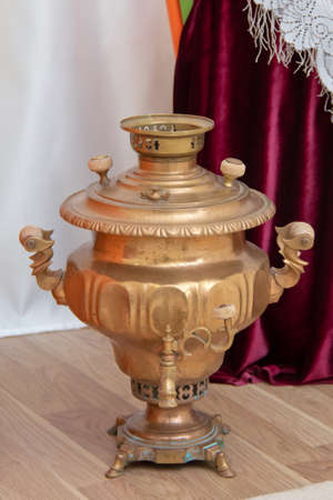 Samovars are typically crafted out of plain iron, copper, polished brass, bronze, silver, gold, tin, or nickel .Gold color Metal samovar on a background