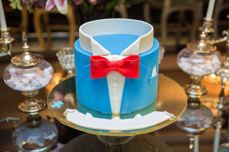 Beautiful blue cake for men, decorated in the form of a suit with a bow tie. The concept of the desserts for the birthday boy