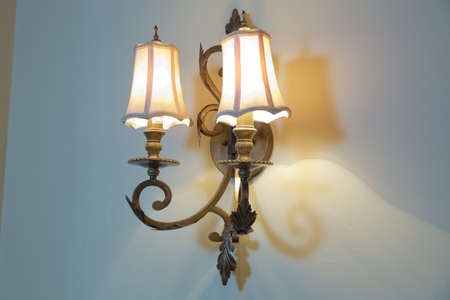 The lamp shines in the dark . Vintage Wall Lamp . light bulb design in vintage style on wall . antique lamp . close up on vintage light on the wall