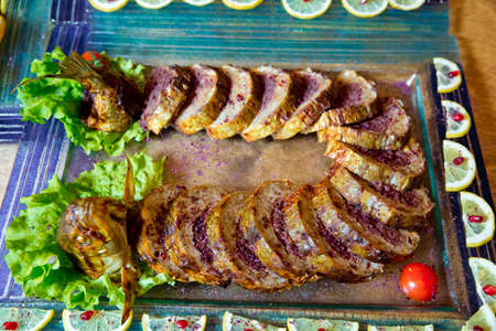 Cooked baked grilled fish . Grilled salmon fish and various vegetables on wooden table . chopped, baked live fish