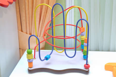 Child counting learning multi color wood bead toy isolated on white background . Picture of a Classic Toy for Young Child . A childs bead roller coaster toy in primary colors