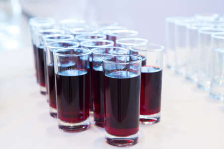 Group of glasses with cherry juice on the table . glasses of cherry juice .Row of Glasses with Fresh cherry Juice. Catering concept. Bokeh blurred background. Selective focus .