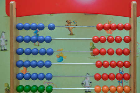 Traditional abacus with colorful wooden beads on white background. Toy abacus to learn counting. Colorful children counting frame for kids. Top side view.abacus with red green blue and balls 스톡 콘텐츠