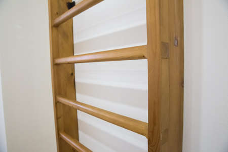 wooden back in the school gym for student exercises . wooden wall bars ladder in big empty gym room of school