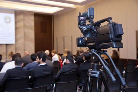 Behind the scene. Shooting the film scene with camera in film studiocamera in a concert or conference hall.Video cameras operator working with his equipment. Selective focus