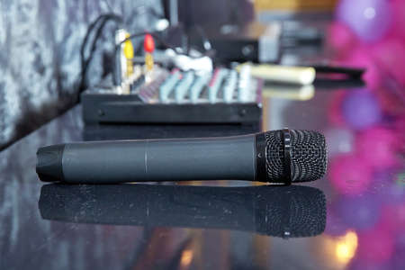 A black microphone is on the table .Close up Microphone on the table, concept of speaker or teacher preparation to speak in seminar class room 스톡 콘텐츠