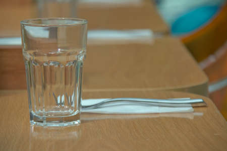 Empty glass on the wooden table in cafe. close up . glass on top of wooden table with blurry restaurant