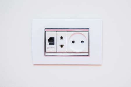 Electric light switch and socket on the empty wall, electrical power socket and plug switched . a socket on a light gray wall, a multifunction outlet with an internet connection .