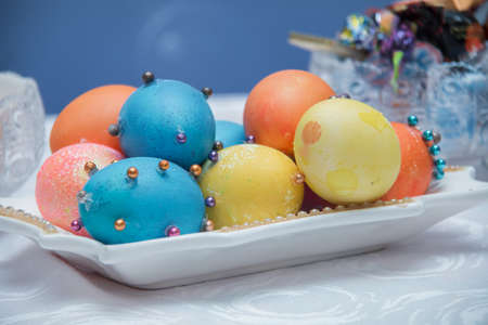 Image of several color eggs placed on plate . Hand colored Easter eggs on vintage plate.Many Colorful Easter Eggs On White Plate Placed By Heap and marble background 스톡 콘텐츠
