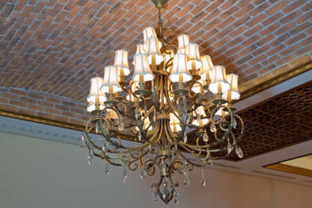 Chandelier on the ceiling .Chandelier in the Italian style. Vintage chandelier. Retro ceiling lamp . Beautiful expensive royal chandelier hanging at the ceiling in the dark room