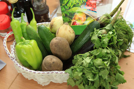 In the basket are peppers, cucumbers, onions, potatoes, greens, pickles eggplant fresh vegetables