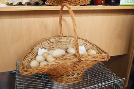 Basket of white eggs on wooden table . eggs in a wicker basket . Easter eggs.White eggs in basket.Closed up . Yellow and white egg yolk 스톡 콘텐츠