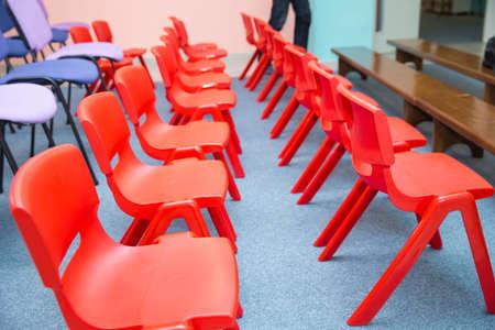 Red chairs in Montessori Kindergarten Preschool Classroom . kindergarten class with the red kids chairs . 스톡 콘텐츠