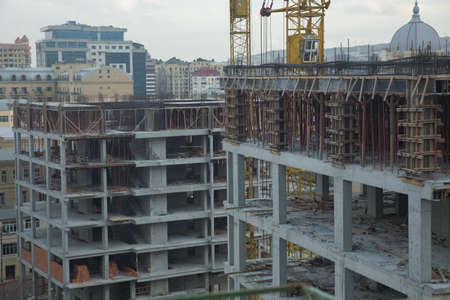 New building is being constructed. Large construction site including several cranes working on a building complex. Working on a construction site 스톡 콘텐츠