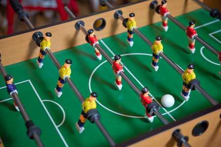 Soccer table kids home toys, football family game table toys childrens board . Table soccer. Foosball in a childrens playroom. Close-up during the game.