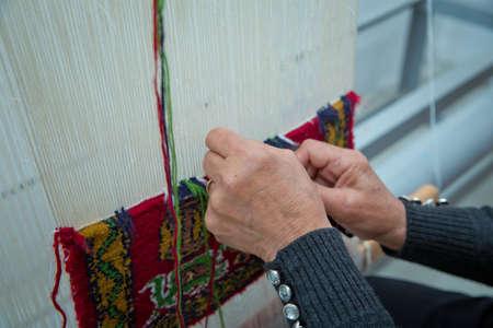 Frauenhände, die Teppich weben. Weben und Herstellung von handgefertigten Teppichen Nahaufnahme. Frauenhände weben einen Teppich