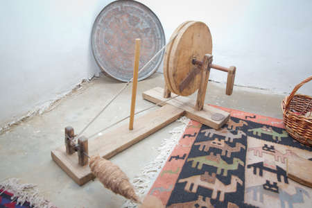 Old Azerbaijan spinning wheel for wool . the old wooden wool winding machine with materials .Old fashioned wooden distaff, spindle, spinning wheel . wool thread in the basket Reklamní fotografie