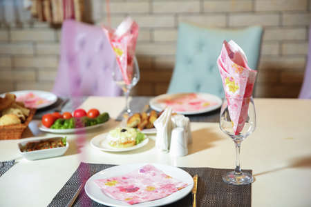 Glass with paper napkins on table against .Pink tissue papers in glass .wedding table - decoration with glasses and paper napkin . napkin on the plate .