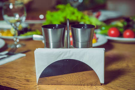 A table in a cafe or restaurant. White napkins in a metal napkin holder, spices salt and pepper on a wooden table, panoramic view . metal napkin holder isolated on white background.