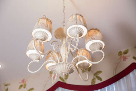 Chandelier Lamp beautiful luxury expensive chandelier hanging under ceiling . The lamp in the beautiful room . Modern Brass chandelier . Chandelier ceiling lights