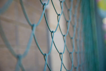 Blue metal fence net as background. Detail of a fence with abstract background.close up steel fence agains green field : narrow depth of field .Grille and background blurred Banco de Imagens