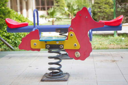 Spring horse in the playground. Seesaw on child playground in park. childs horse ride in the playground .Swing on a metal spiral