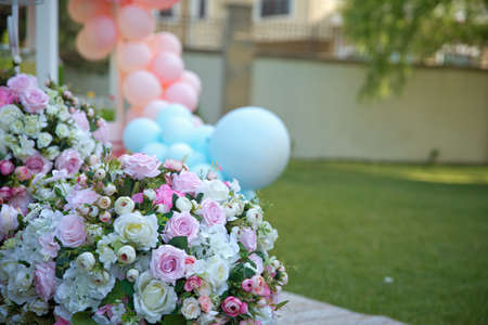 Closeup of picnic basket with white flowers on the grass . Pink and white Flowers Basket Green Grass Garden Summer . Summer Picnic on the lawn. blue balloon . Stock Photo