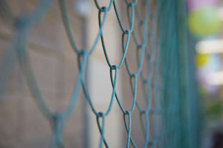 Blue metal fence net as background. Detail of a fence with abstract background.close up steel fence agains green field : narrow depth of field .Grille and background blurred Zdjęcie Seryjne
