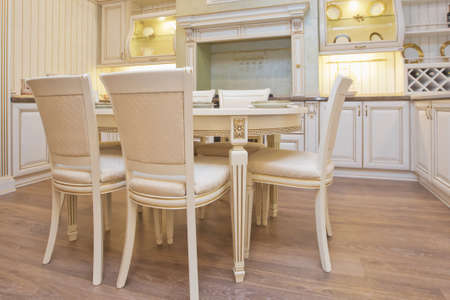 Italian kitchen furniture . White Furniture of the classic italian kitchen. Modern style . Home decoration. Modern home interior. Modern kitchen design in a light interior. Wood cupboard. White table and chair Zdjęcie Seryjne