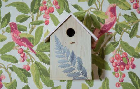 handmade bird wood home on green nature wall . Wooden bird nest on the wall.