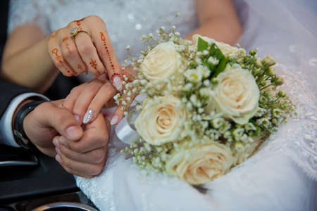 Wedding couple holding hands .Bride and groom hands with wedding rings and bridal dress . Bride and grooms hands with wedding rings 版權商用圖片